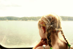 Young girl looking through a boat window. Royalty Free Stock Photography
