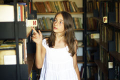 Young girl looking for a book of old library Stock Photos