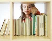 Young girl looking at books on bookshelf Stock Image