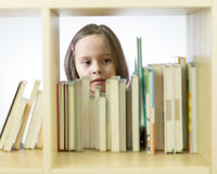 Young girl looking at books on bookshelf Stock Images