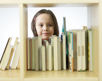 Young girl looking at books on bookshelf Royalty Free Stock Image