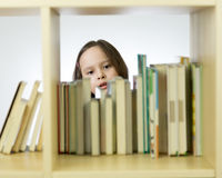 Young girl looking at books on bookshelf Stock Photos