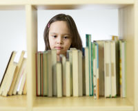 Young girl looking at books on bookshelf Royalty Free Stock Photos