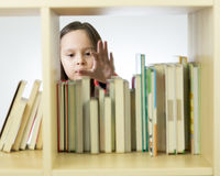 Young girl looking at books on bookshelf Stock Photo