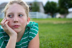 Young girl looking bored. An adolescent girl looking bored in a field Royalty Free Stock Photos