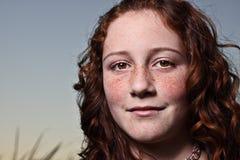 Young girl looking at the camera. Young redhead glancing towards the camera Stock Photos