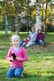 Young girl looking at camera when sitting on grass with cellphone, family on background Royalty Free Stock Photography