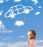 Young girl looking at car cloud on a blue sky Royalty Free Stock Images