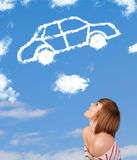 Young girl looking at car cloud on a blue sky. Casual young girl looking at car cloud on a blue sky stock photos