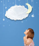 Young girl looking at cartoon night clouds with moon Stock Images