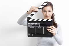 Young girl looking through clapper board Royalty Free Stock Photos