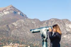 Young girl looking through a coin operated binoculars. Bellagio Stock Photos