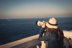 Young girl looking through a coin operated binoculars on the sea Royalty Free Stock Photo