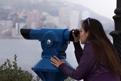 Young girl looking through a coin operated binoculars Stock Image