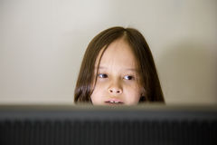 Young girl looking at computer screen Royalty Free Stock Images