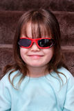 Young girl looking cool with sunglasses on indoors. Pretty little girl smiling and wearing sunglasses whilst sitting on the stairs Stock Photo