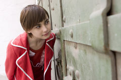 Young girl looking  through the door Royalty Free Stock Photo