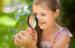 Young girl is looking at flower through magnifier Royalty Free Stock Images