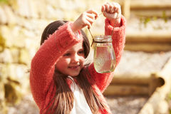 Young Girl Looking At Frogspawn In Jar Stock Photography