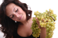 Young girl looking at grapes. A young female is looking at the grapes Royalty Free Stock Photo