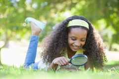 Young girl looking at grass through magnifying glass in the park Stock Photo