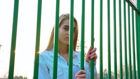 Young Girl Looking Through the Grid stock footage