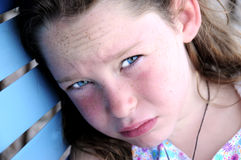 Young girl looking hot and tired. Young freckle faced girl sitting outside on bench looking hot and tired Stock Images