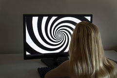 Young girl is looking at hypnosis spiral on her computer. Young girl with long blond hair is looking at hypnosis spiral on her computer stock photo