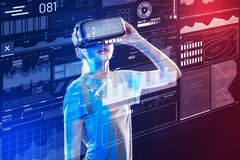 Young girl looking impressed while wearing virtual reality glasses. Using virtual reality. Progressive young girl wearing virtual reality glasses and feeling Royalty Free Stock Image