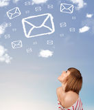 Young girl looking at mail symbol clouds on blue sky Stock Images
