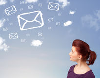 Young girl looking at mail symbol clouds on blue sky Royalty Free Stock Images