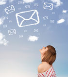 Young girl looking at mail symbol clouds on blue sky Stock Photo