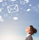 Young girl looking at mail symbol clouds on blue sky Royalty Free Stock Photo