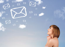 Young girl looking at mail symbol clouds on blue sky Royalty Free Stock Photos