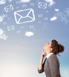 Young girl looking at mail symbol clouds on blue sky Royalty Free Stock Image