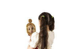 Young girl looking in the mirror. Isolated on white Royalty Free Stock Photos