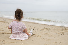 Young girl looking out to sea stock images
