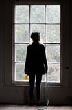 Young girl looking out window. Stock Image