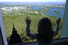 Young girl looking out of a window at Canberra the capital city of Australia. Silhouette of a young girl looking out of a window at aerial landscape view from stock photography