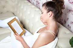 Young girl looking at photoframe. Royalty Free Stock Photo