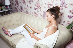 Young girl looking at photoframe. Smiling beautiful young woman lying on sofa, relaxing, looking at photoframe Royalty Free Stock Photo