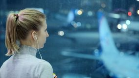 Young girl is looking at a plane at the airport. Listens to music through headphones. Waiting for my flight. Young girl is looking at a plane at the airport stock video
