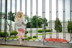 Young girl looking at the Presidential Palace, located in Vilnius Old Town, the official office and eventual residence of the. Young girl looking at the stock photos