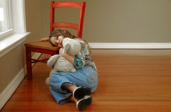 Young Girl Looking Sad. Young girl alone in room looking sad holding stuffed toy Royalty Free Stock Image