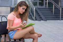 Young girl looking for sales using tablet while calling someone. Royalty Free Stock Images