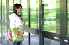 Young girl looking a showcase. Young woman with shopping bags looking a showcase royalty free stock images
