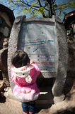 Young girl looking stone map in Lijiang Dayan old town.. Stock Photos