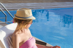 Young girl looking at the swimming pool from the sunbed. Girl at. Young girl looking at the swimming pool from the sunbed wearing straw hat Royalty Free Stock Photo