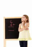 Young Girl Looking Thoughtful Next To Blackboard Stock Image