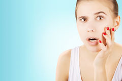 Young girl looking to her skin with astonishment, blue backgroun Stock Images